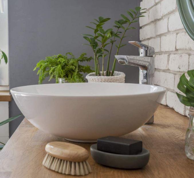 Una imagen preciosa de un lavabo redondo sobre una encimera de madera decorada con plantas y accesorios de baño de diseño.