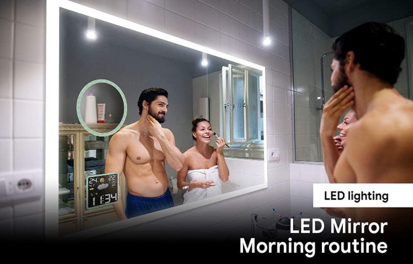 Un espejo de baño moderno que incluye tecnologías avanzadas decorando un cuarto de baño y siendo utilizado por una pareja feliz aseándose.