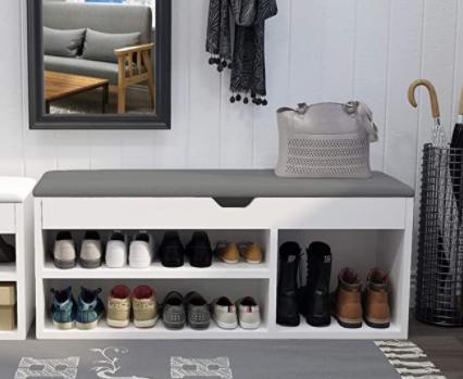 Un banco zapatero con arcón de color blanco y asiento gris acolchado organizando varios zapatos y botas altas. en un recibidor.